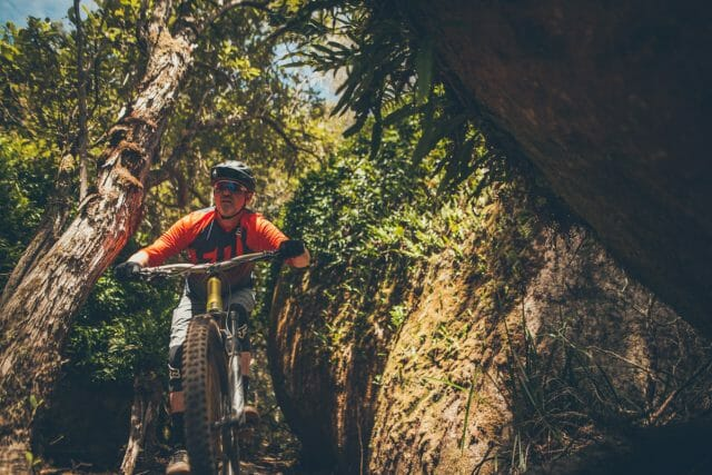 Darryll squeezes his Canyon Spectral through a big leafy boulder.